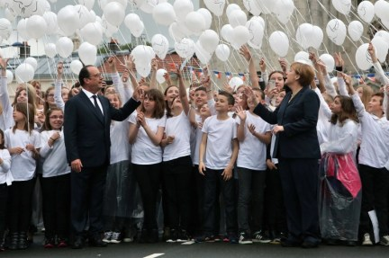 France's President Francois Hollande (L) and German Chancellor Angela Merkel (R) attend a ballon drop during a remembrance ceremony to mark the centenary of the battle of Verdun, in Verdun, on May 29, 2016. The battle of Verdun, in 1916, was one of the bloodiest episodes of World War I. The offensive which lasted 300 days claimed more than 300,000 lives. / AFP PHOTO / POOL / Thibault Camus